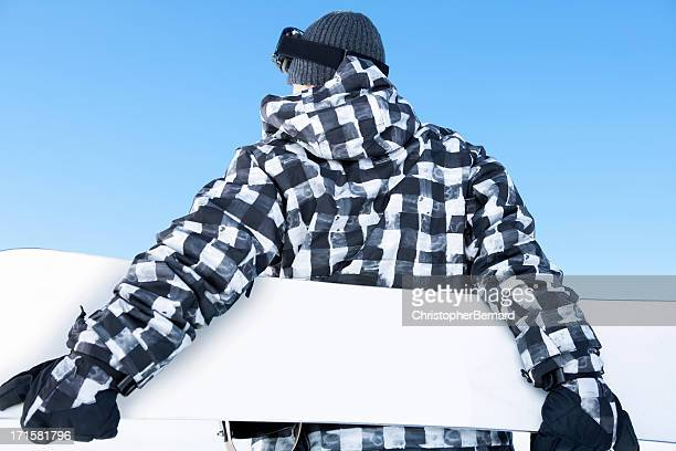 Backview of male snowboarder against blue sky