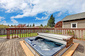 Backyard wooden deck with jacuzzi on it. Close up view of open jacuzzi and water in it.