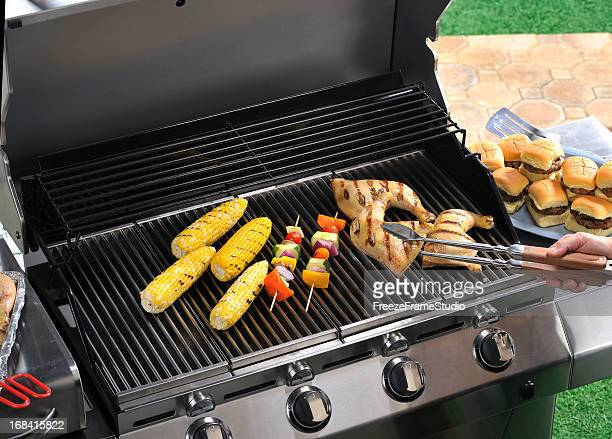 Backyard grilling scene with bbq kabobs, corn and chicken