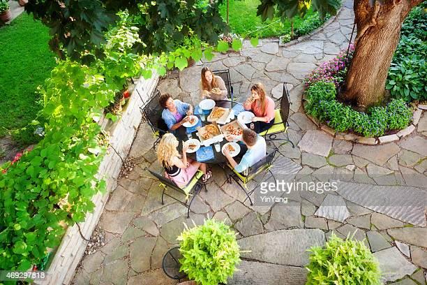 Patio Patio, vista al jardín, con vegetación y adolescentes disfrutar de pizzas