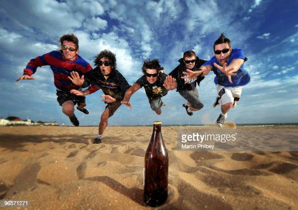 Backyard Surgeons pose for a group shot leaping for a bottle of beer on a beach on 8th February 2009 in Melbourne Australia