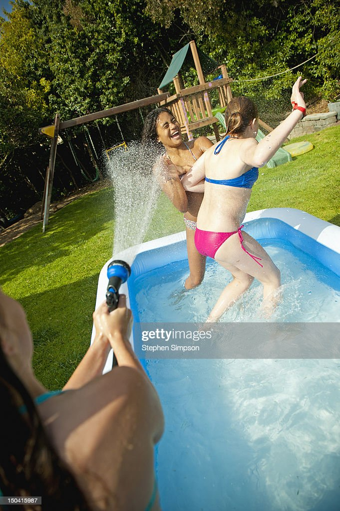 backyard water fight between 11-year-old girls : Stock Photo