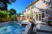 Cozy backyard with patio area and jacuzzi. Walkout deck with flower pots