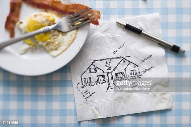 Bacon and eggs with fork and napkin with pen and sketch of house