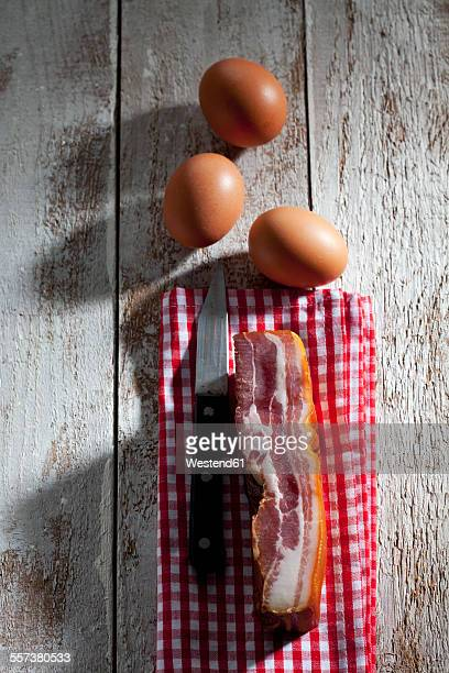 Bacon and kitchen knife on towel and three brown hens eggs on wood