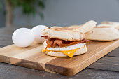 Bacon, egg and cheese breakfast sandwich with english muffin on cutting board