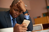Frustrated African-American businessman reading message on his smartphone
