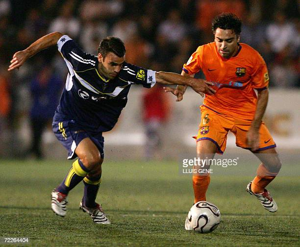 Barcelona's Xavi vies with CF Badalona's Puigdollers during their King's Cup football match at the Camp del Centenari stadium in Badalona near...