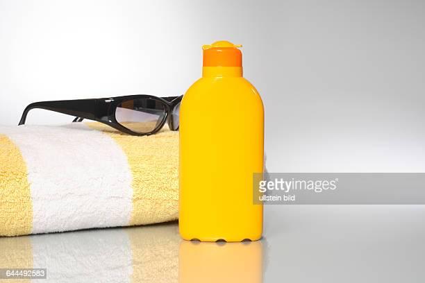 Badelaken mit Sonnenmilch und Sonnenbrille