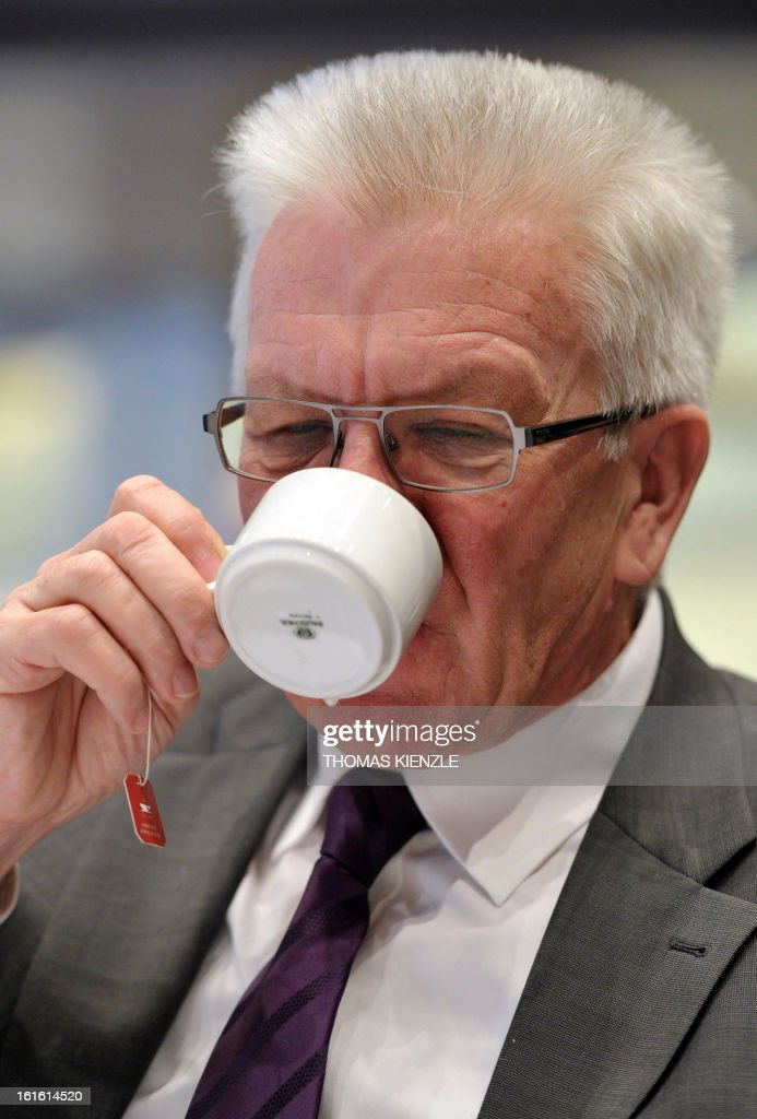 Baden-Wuerttemberg's Prime Minister Winfried Kretschmann of the German Green party drinks a cup of tea at his party's traditional political Ash Wednesday rally in Biberach, southern Germany, on February 13, 2013. AFP PHOTO / THOMAS KIENZLE