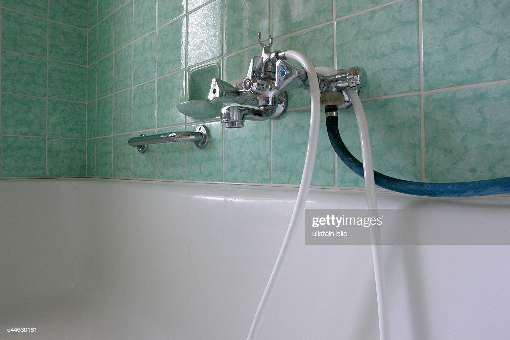 Badezimmer Mit Grünen Kacheln. Wasserhahn An Der Badewanne Mit Weissem  Plastikschlauch Und Waaserschlauch Für Die