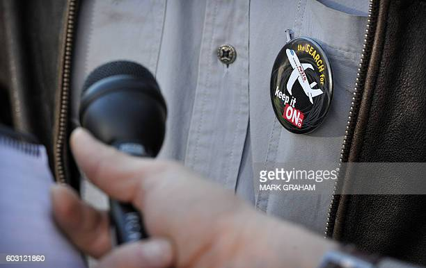 A badge is pictured on the shirt of US amateur investigator Blaine Gibson as he speaks to the media after a meeting with the Australian Transport and...
