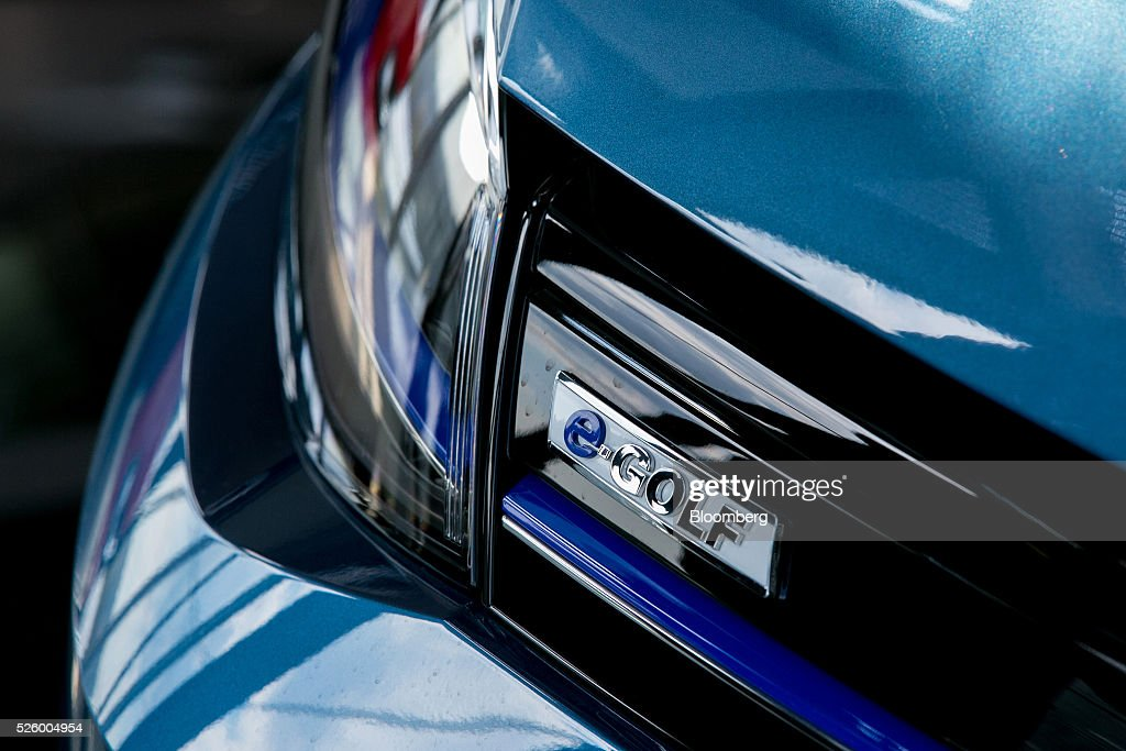 A badge sits on a e-Golf electric automobile, produced by Volkswagen AG (VW), as it stands inside one of the automaker's glass delivery towers at the VW factory in Wolfsburg, Germany, on Friday, April 29, 2016. Porsche Automobil Holding SE, the investment vehicle of the billionaire family that controls VW, stuck to a goal of making acquisitions beyond the beleaguered carmaker, even as its dwindling cash on hand reduces the scope of possible transactions. Photographer: Krisztian Bocsi/Bloomberg via Getty Images