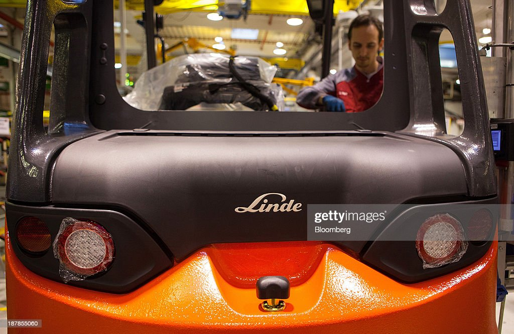 A badge sits on a Linde E25 electric forklift truck as an employee works on the vehicle at the Linde Material Handling GmbH factory, a unit of Kion Group AG, in Aschaffenburg, Germany, on Tuesday, Nov. 12, 2013. Kion Group AG, the German forklift-maker which listed shares in June, is looking to expand its global sales network via acquisitions to catch up with main competitor Toyota Industries Corp. Photographer: Krisztian Bocsi/Bloomberg via Getty Images