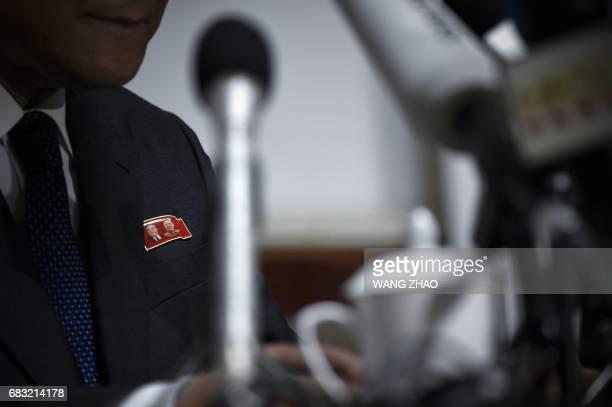 A badge with images of North Korean leaders Kim IlSung and Kim JongIl is worn by North Korea's Ambassador to China Ji JaeRyong during a press...
