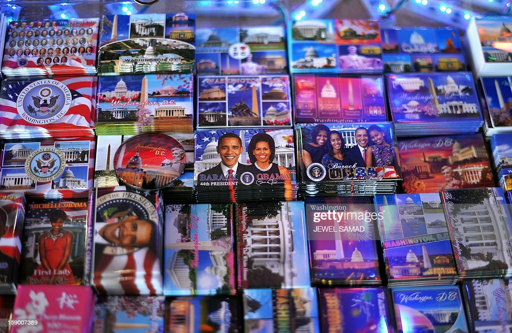 Badges featuring pictures of US President Barack Obama and the First Family are seen at a roadside souvenir stall in Washington on January 5, 2013. Preparations are underway for Obama's second inauguration which will take place with a public ceremonial oath of office on January 21. AFP PHOTO/Jewel Samad