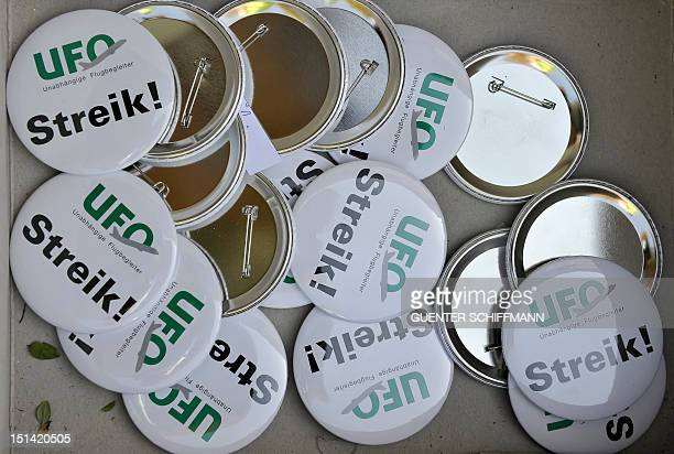 Badges reading 'strike' are seen during a demonstration of German airline Lufthansa striking crew members at the Munich aiport on September 7 2012 as...
