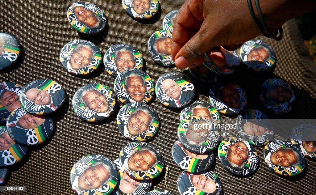 Badges showing the portraits of former South African president Nelson Mandela and current South African president Jacob Zuma with the logo of ruling African National Congress (ANC) party are sold during a march organised by the Congress of South African Trade Unions (COSATU) to support the ruling ANC party in Durban, on April 26, 2014. COSATU (South Africa's largest trade union comprising of over 2 million workers) and the SACP are in a tripartite alliance with the ANC, and have declared their support to the ANC in the upcoming elections on May 7, 2014.
