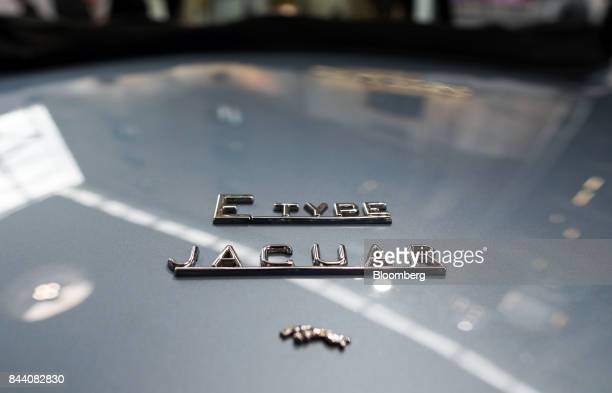 Badges sit on the trunk of a battery version of Jaguar's iconic EType roadster automobile on display at the annual tech fair of Tata Motors Ltd's...