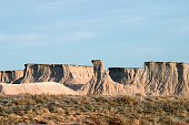 Several flat-topped eroded  buttes as seen in the Badlands National Park in South Dakota.