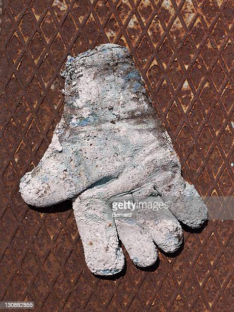 Badly worn work glove on rusty metal plate