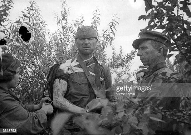 A badly wounded Russian soldier is given aid by a nurse and army doctor during the first weeks of the German invasion of Russia At the beginning of...