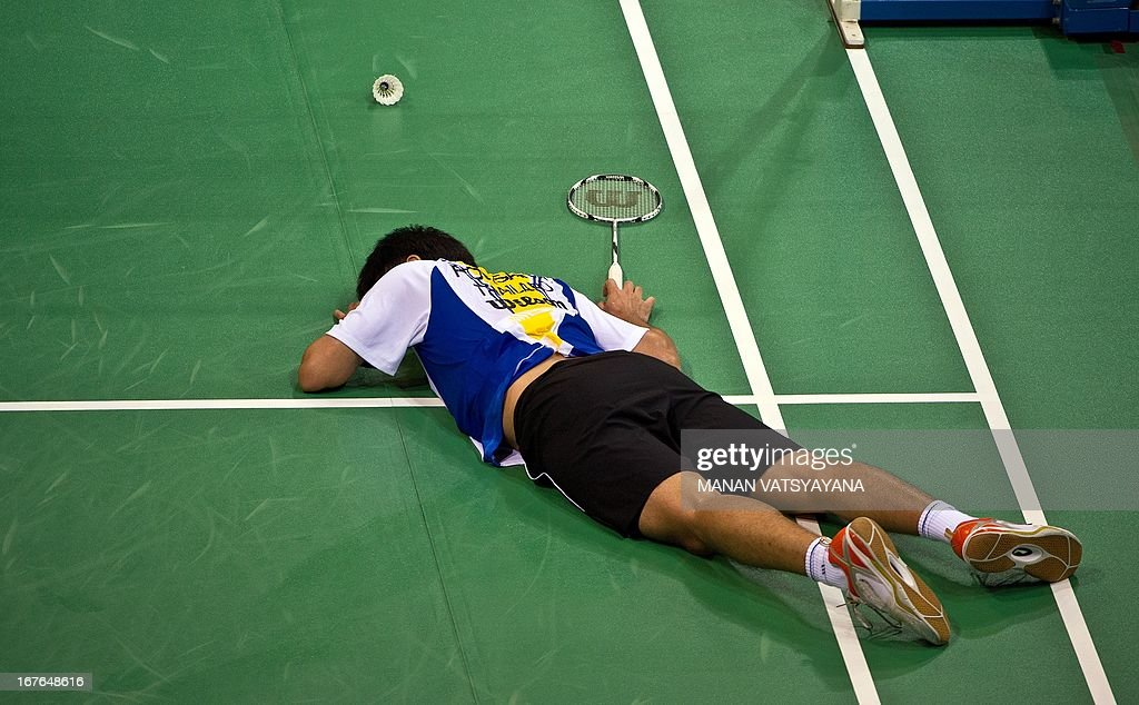 Badminton player Boonsak Ponsana of Thailand lies on the court after losing a point to opponent Lee Chong Wei of Malaysia during their Men's Singles semi-final match of the Yonex-Sunrise India Open 2013 at the Siri Fort Sports Complex in New Delhi on April 27, 2013. Wei won 21-11,18-21,21-8.