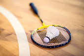 Close-up shot of a badminton racket and a shuttlecock on a wooden court flooring.
