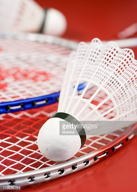 Badminton shuttlecock on red racquet on red surface