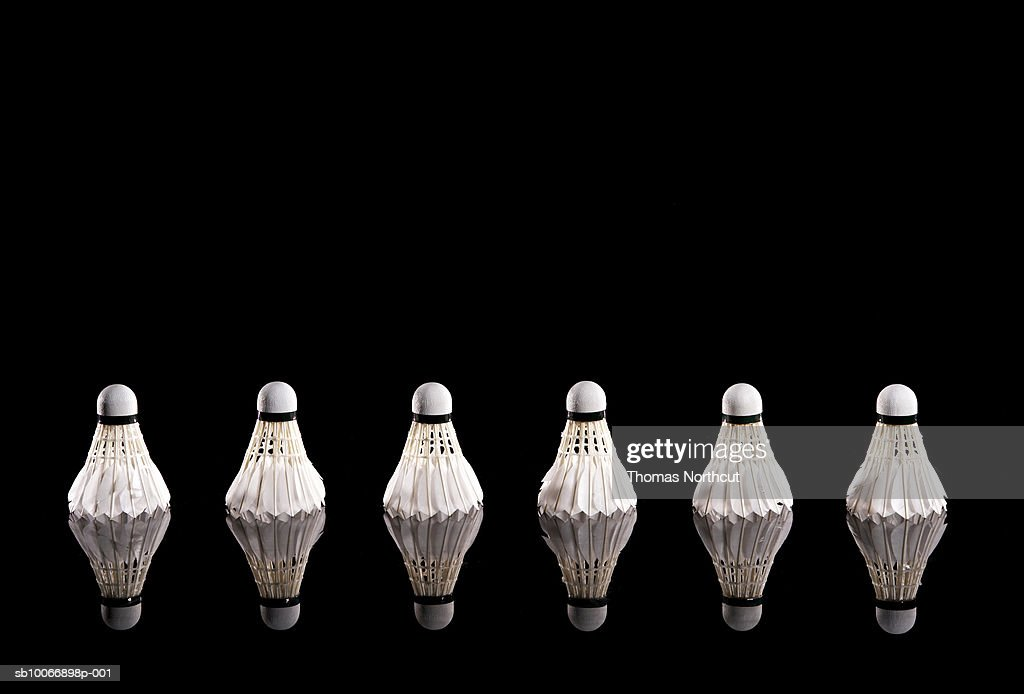Badminton shuttlecocks in row on black background