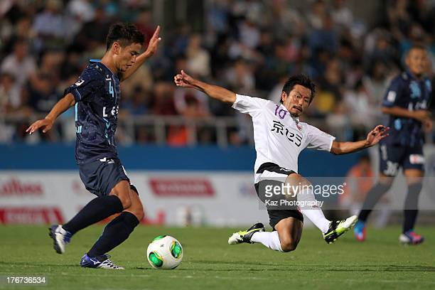 Bae SeungJin of Yokohama FC is tackled by Kohei Kudo of Kyoto Sanga during the JLeague second division match between Yokohama FC and Kyoto Sanga at...
