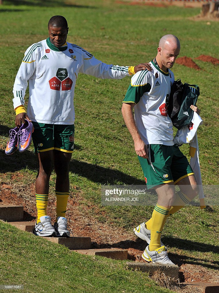 Bafana Bafana (The Boys, nickname of the South African national football team) captain Aaron Mokoena (L) gets an helping hand from defender Matthew Booth (R) during a training session in Johannesburg on May 20, 2010. South Africa occupy Group A with former winners France as well as Uruguay and Mexico, all top-20 national teams in the latest rankings from world rulers FIFA.