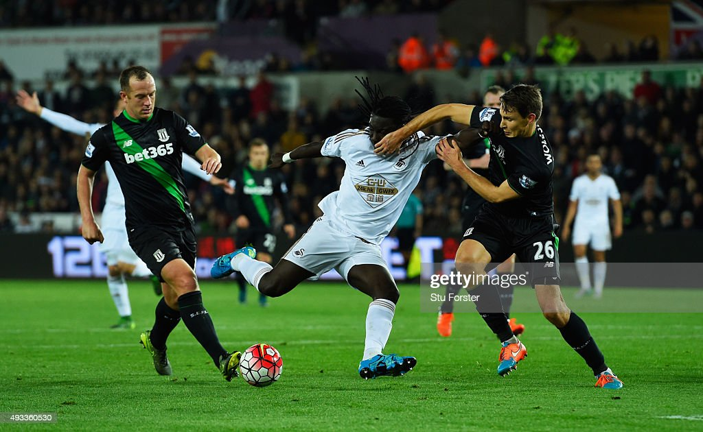 Bafetimbi Gomis of Swansea City is blocked by Philipp Wollscheid (26) and Charlie Adam of Stoke City during the Barclays Premier League match between Swansea City and Stoke City at Liberty Stadium on October 19, 2015 in Swansea, Wales.