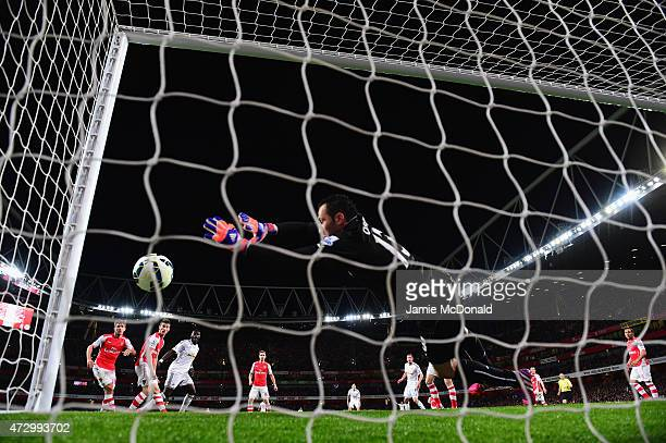 Bafetimbi Gomis of Swansea City scores the first goal as goal line technology rules the ball to cross the line depsite David Ospina of Arsenal making...