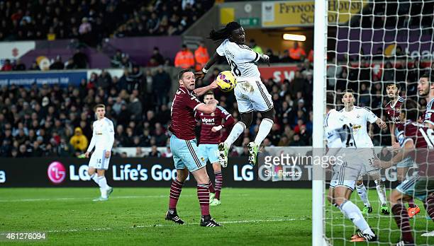 Bafetimbi Gomis of Swansea outjumps Kevin Nolan to score during the Barclays Premier League match between Swansea City and West Ham United at Liberty...