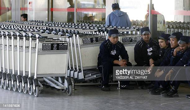 Bag handlers sit near their trollies as airport employees go on strike demanding an increase in salaries and benefits at Kuwait's International...