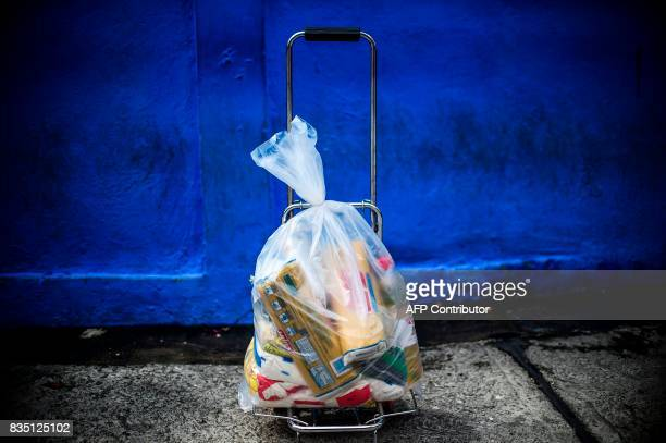 A bag of basic foodstuff loaded on a mobile travel cart is pictured outside one of the food distribution centers called CLAP which are run by...