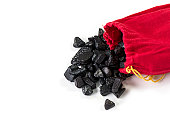 Coal spilling out of a red sack isolated on white with copy space