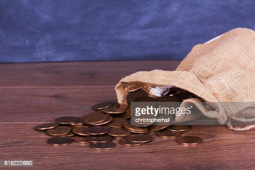 Bag of coins spilt over a wooden surface : Stock Photo