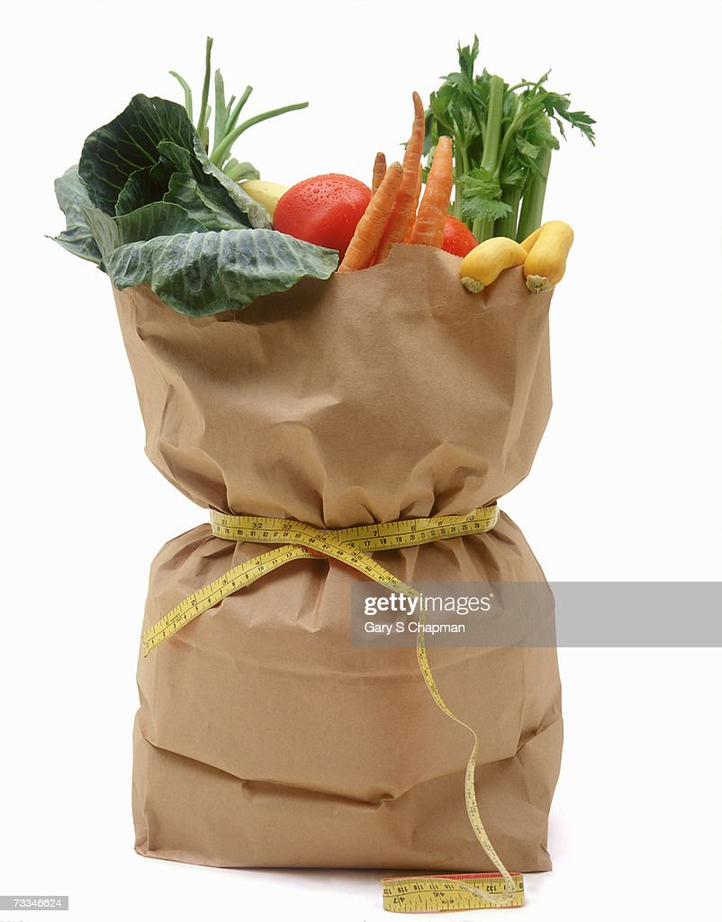 Bag of groceries full of vegetables tied up with measuring tape, close-up : Stock Photo