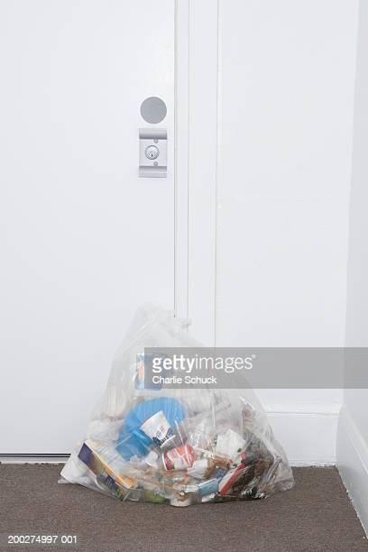Bag of rubbish on floor outside door