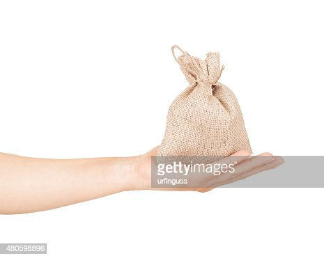 Bag with coins in hand isolated on white : Stock Photo