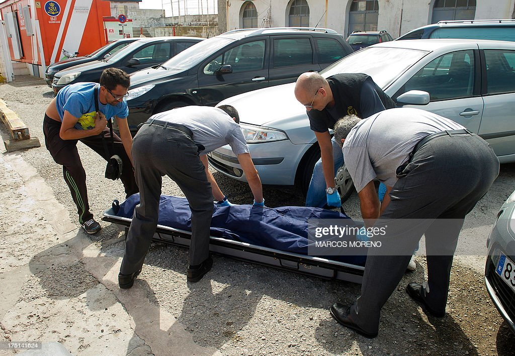 A bag with the body of a would-be immigrant is placed on a stretcher by Spanish Guardia civil and Spanish rescuers in Tarifa, on August 1, 2013. Spanish rescuers intercepted today a boat carrying 8 sub-Saharan would-be immigrants, accross the Strait of Gibraltar. One of them died before arriving to the harbour of Tarifa.