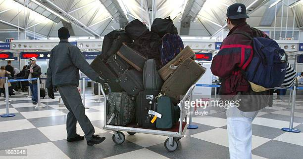 Baggage handler Derrick Dixon pulls his cart full of luggage through the United Airlines terminal November 27 the day before Thanksgiving one of the...