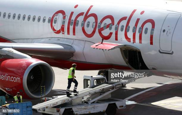 A baggage handler prepares to remove luggage from an Air Berlin airplane on the tarmac at Tegel Airport on August 23 2017 in Berlin Germany Air...