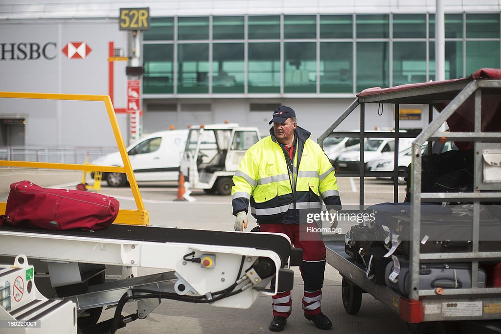 A baggage handler watches luggage on a conveyor belt as it comes off a Ryanair Holdings Plc passenger aircraft at Stansted Airport, operated by Manchester Airports Group (MAG) in Stansted, U.K., on Tuesday, Sept. 10, 2013. From two planes in 1995, EasyJet has grown to more than 200 Airbus SAS aircraft carrying more than 59 million people annually, 20 million fewer than Ryanair. Photographer: Simon Dawson/Bloomberg via Getty Images