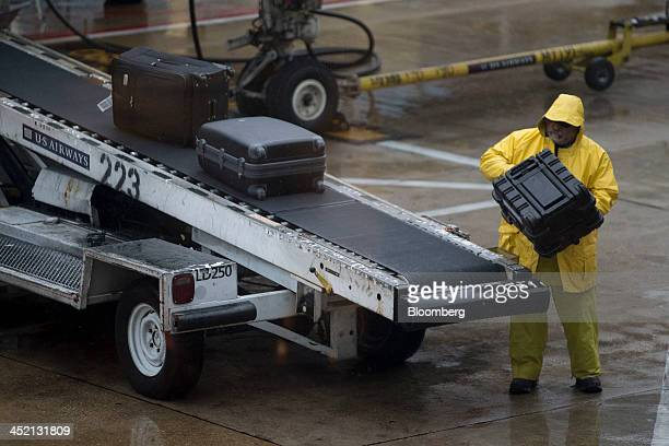 A baggage handler wears a rain suit while loading bags onto a US Airways Group Inc airplane at Ronald Reagan National Airport in Washington DC US on...