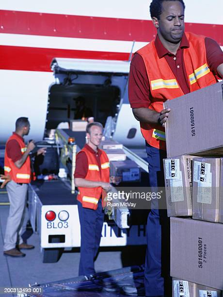 Baggage personnel loading aeroplane at airport