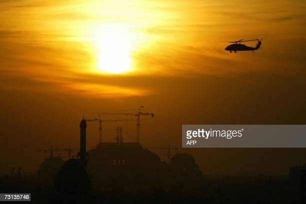 A US Blackhawk helicopter flies over the skies of Baghdad at sunset 28 January 2007 At least 24 Iraqis were killed in ambushes car bombs and...