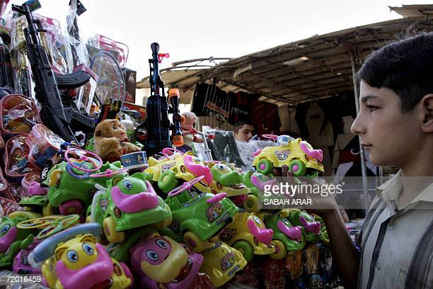 An Iraqi boy looks at toys at a shop in a public market in Baghdad 27 September 2006 Brutal attacks and high prices have cast a shadow over Iraq's...